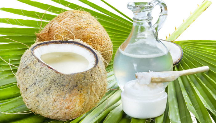 Coconut water in flask with coconut fruit and coconut oil on palm leaf