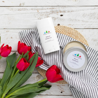 Three Gems Natural Deodorants With Red Tulips On White Wooden Background