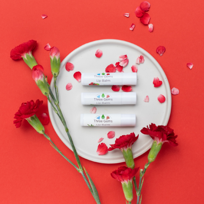 Three Gems Lip Balms in Aloe Vera, Spearmint and Strawberry dispayed on a white plate with red background